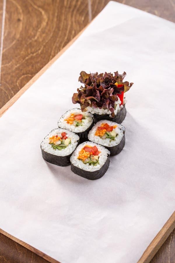 Petit pain japonais de vegan avec les légumes et la salade sur le livre blanc sur la table en bois photos libres de droits