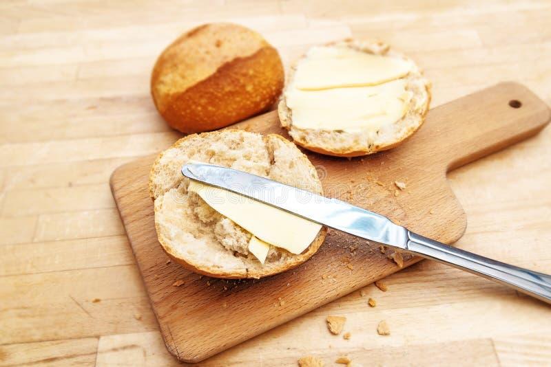 Petit pain ou petit pain de pain avec du beurre et le couteau sur une planche à découper sur a photographie stock libre de droits