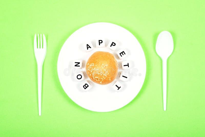 Petit pain rond du plat blanc avec la FÈVE APPETIT de cuillère, de fourchette et de textes Boulangerie, concept d'heure du déjeun photo libre de droits
