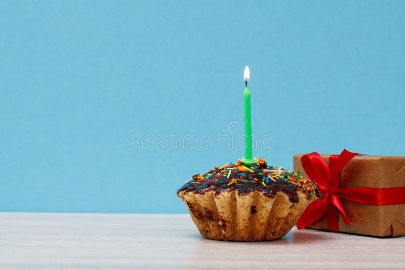 Petit pain savoureux d'anniversaire avec brûler la bougie et le boîte-cadeau de fête sur le fond bleu photos stock