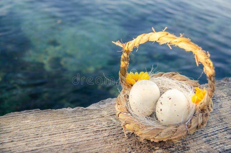 Petit panier avec deux oeufs de pâques sur le Doc. de mer l'heure d'or photo stock