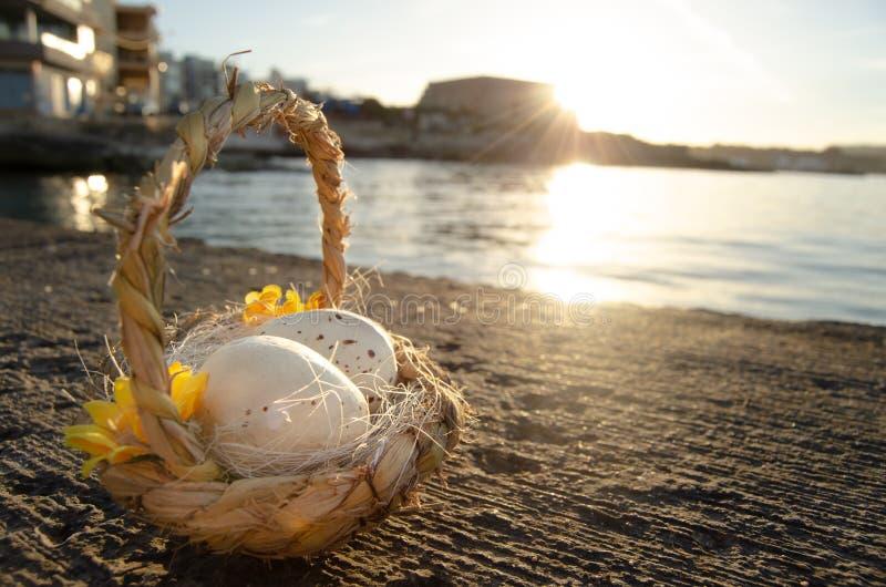 Petit panier avec deux oeufs de pâques sur le Doc. de mer l'heure d'or photographie stock libre de droits