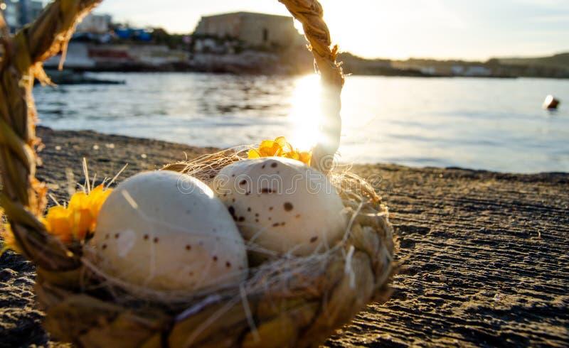 Petit panier avec deux oeufs de pâques sur le Doc. de mer l'heure d'or images libres de droits