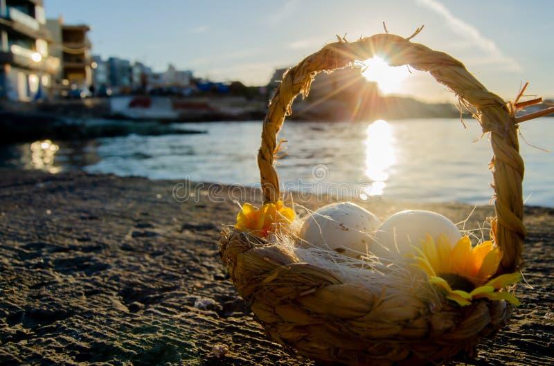Petit panier avec deux oeufs de pâques sur le Doc. de mer l'heure d'or image libre de droits