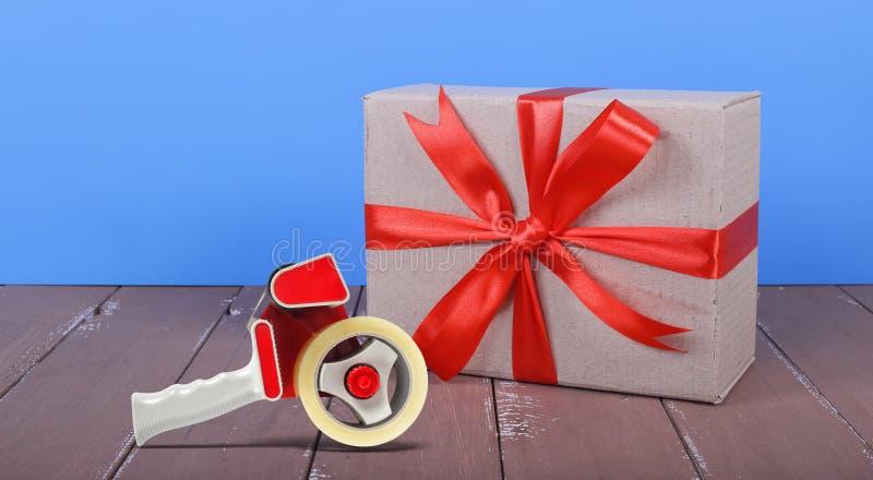 petit paquet attaché par un distributeur rouge d'arc et de bande sur un bois brun et un mur bleu photos libres de droits