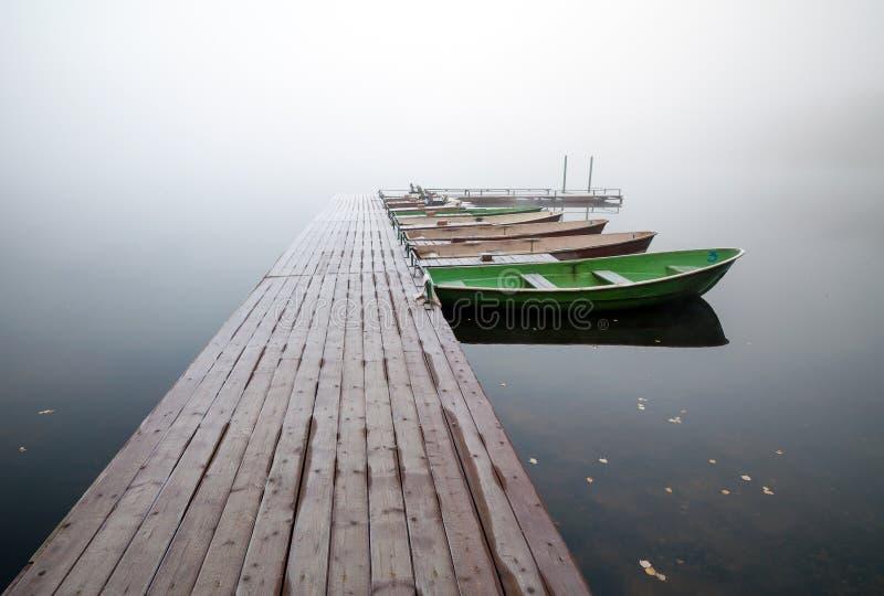 Petit pilier avec des bateaux sur le lac en matin brumeux image stock