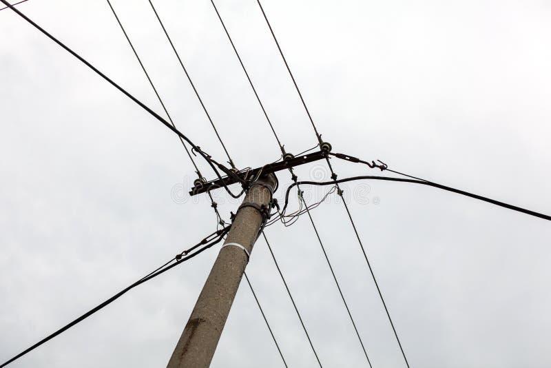 Petit pilier concret avec des lignes électriques, ciel obscurci dans le backgrou photos libres de droits