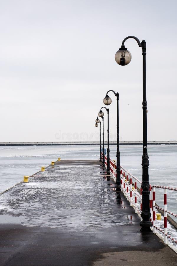 Petit pilier dans le port de passager Les lanternes à la couchette pour amarrent photographie stock libre de droits