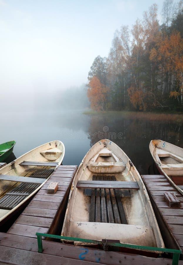 Petit pilier en bois avec des bateaux à rames sur le lac immobile image stock