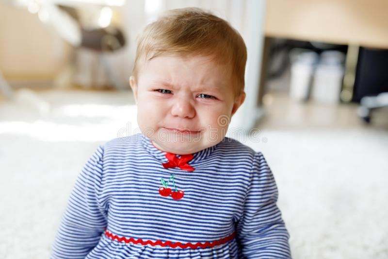 Petit pleurer triste mignon de bébé Enfant affamé ou fatigué s'asseyant à l'intérieur et ayant des larmes photographie stock libre de droits