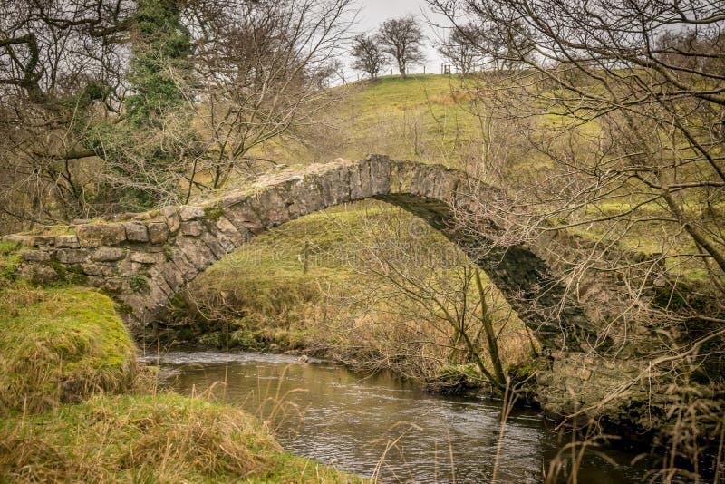 Petit pont en pierre de pied au-dessus d'un petit courant photo libre de droits