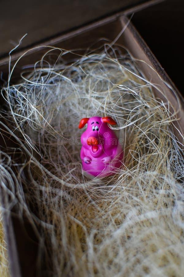 Petit porc de figurine de rose de jouet en paille dans la boîte en bois comme une grange images libres de droits