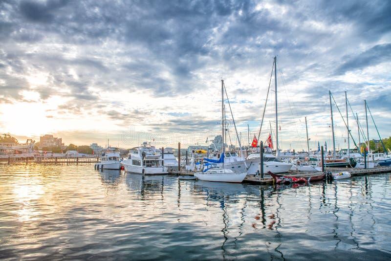 Petit port de ville avec les bateaux accouplés au coucher du soleil contre le ciel nuageux photos stock