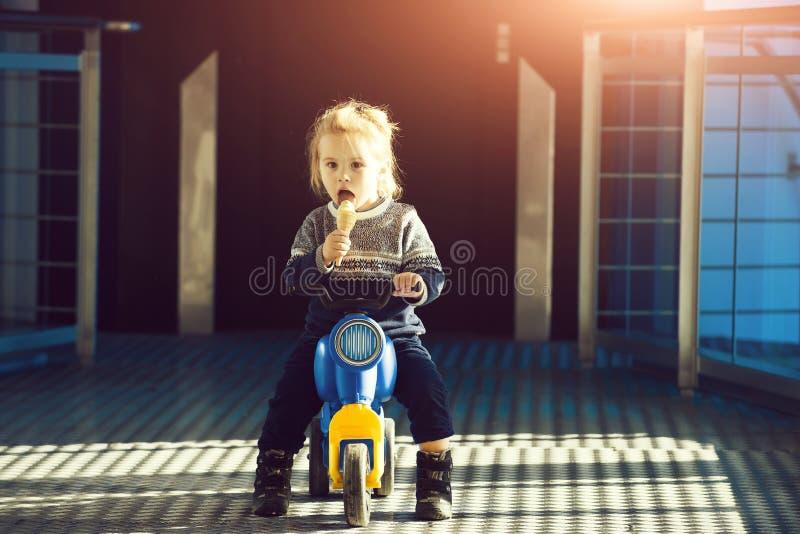 Petit portrait de garçon mangeant la crème glacée, se reposant sur le vélo de jouet photo stock