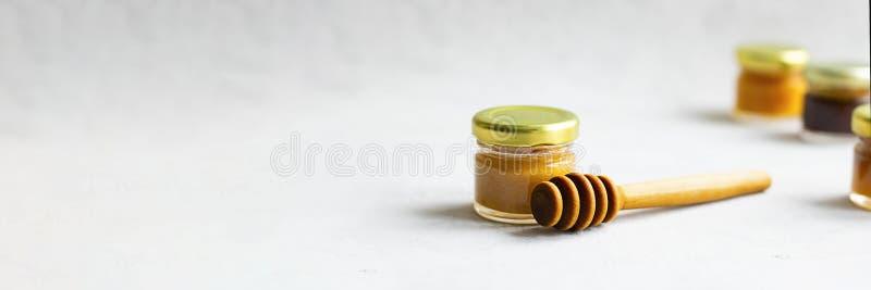 Petit pot en verre avec le chapeau en métal avec du miel jaune-clair et la cuillère en bois spéciale et trois defocused loin sur  images libres de droits