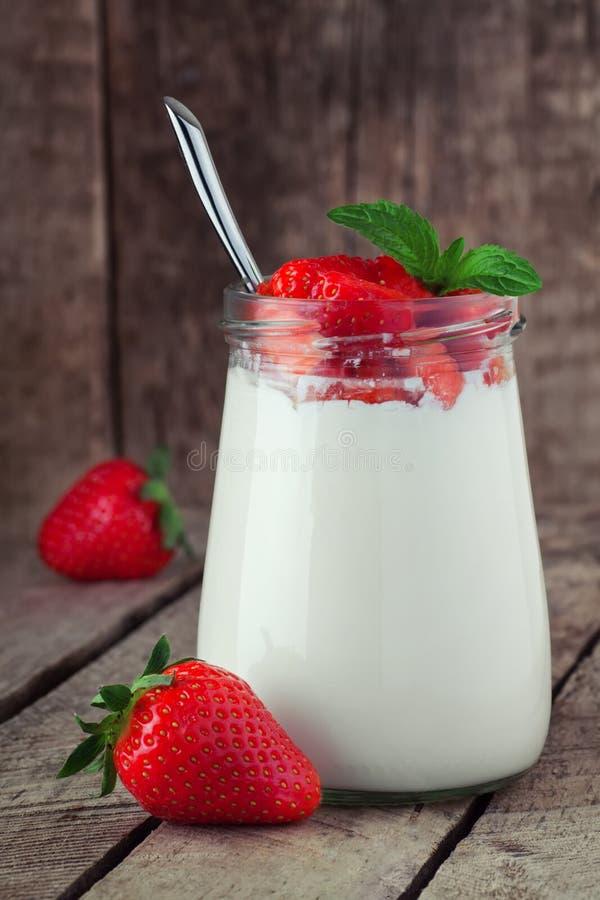 Petit pot sur la table en bois avec du yaourt avec la fraise fraîche image libre de droits