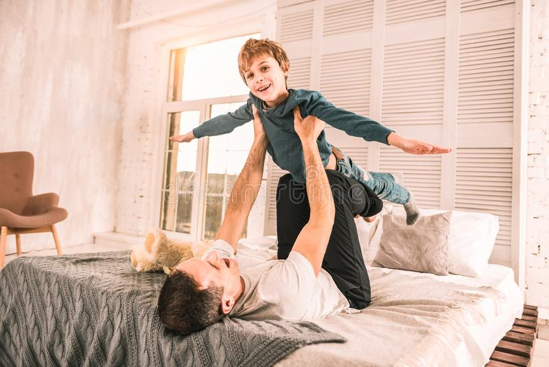Petit rêveur enthousiaste feignant pour être un avion tout en jouant avec son père image libre de droits
