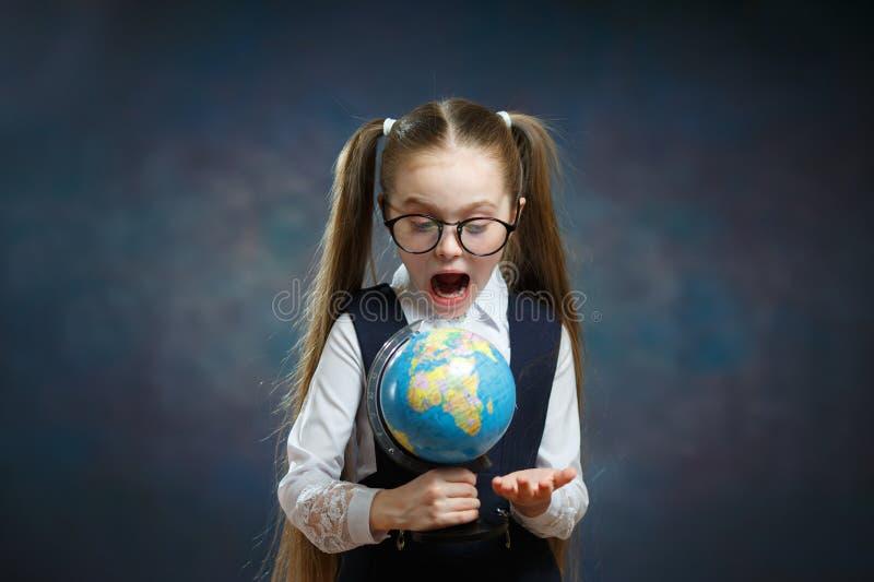 Petit regard blond stupéfait d'écolière au globe du monde photographie stock