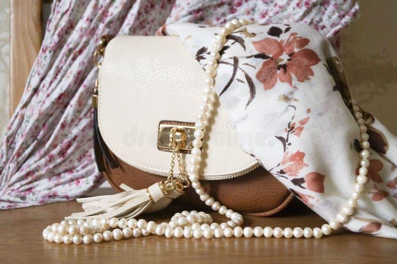Petit sac à main de dames et une ficelle des perles et du textile images libres de droits