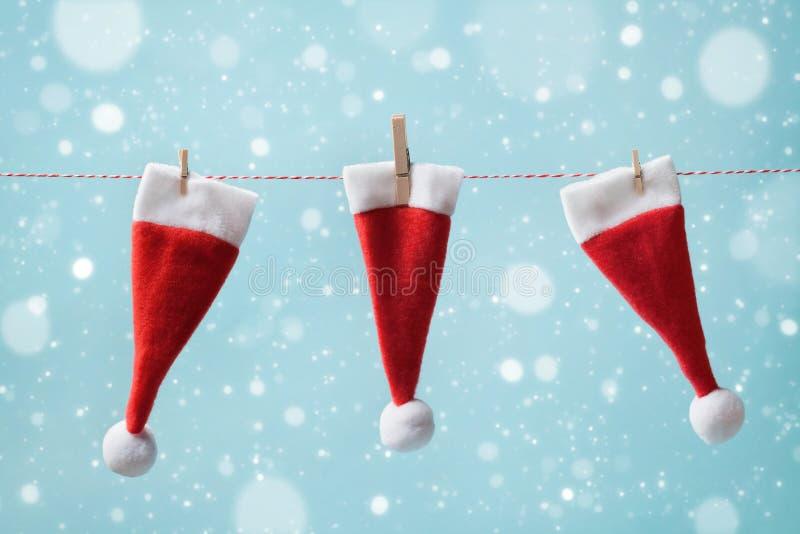 Petit Santa Claus chapeau de trois accrochant sur une ficelle sur le fond neigeux bleu Concept de Noël et d'an neuf Carte de voeu image stock