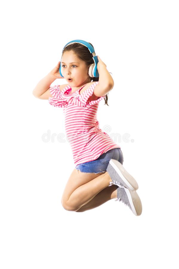 Petit sauter drôle et crier peu de fille caucasienne avec écouteurs photo libre de droits