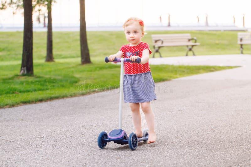 petit scooter actif d'équitation de fille d'enfant en bas âge sur la route en parc dehors le jour d'été images stock