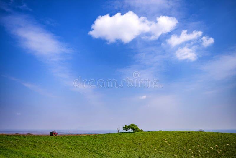 Petit seul tracteur rouge sur le dessus des terres cultivables accidentées avec les nuages blancs magnifiques et le panorama de c photos libres de droits