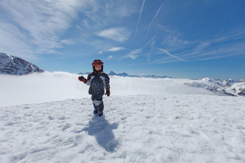 Petit skieur mignon et panorama alpin photographie stock