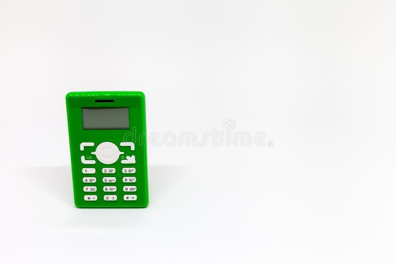 Petit t?l?phone portable vert sur le fond blanc photos stock