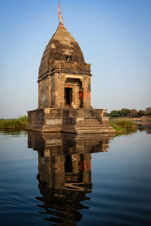 Petit temple hindou au milieu de la rivière sainte Narmada, Maheshwar, État du Madhya Pradesh, Inde photographie stock libre de droits
