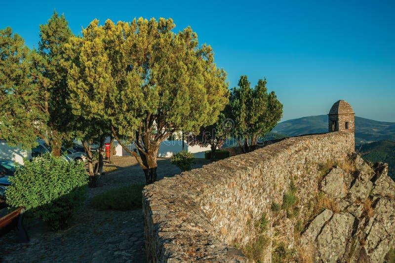 Petit tour de guet et mur en pierre au-dessus de falaise avec peu de place en bois images libres de droits