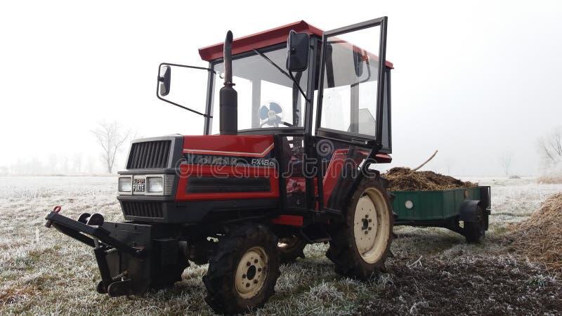 petit tracteur sur le champ d'hiver photos stock