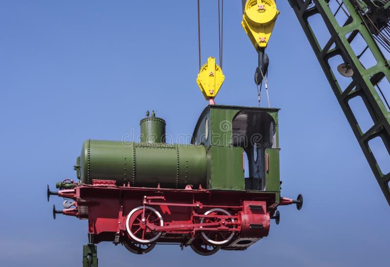 Petit train nostalgique vert mignon de vapeur accrochant dans le ciel sur un camion de grue, un skye bleu et un espace de copie,  photos libres de droits