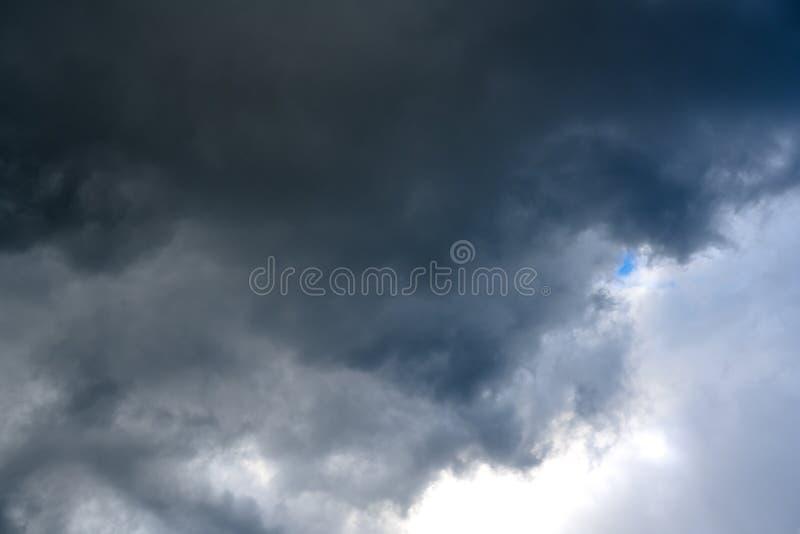 Petit trou bleu minuscule entre les cumulonimbus foncés apportant la pluie photos stock