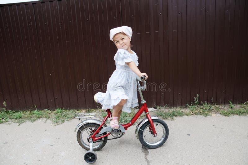 Petit vélo élégant d'équitation de fille Enfant sur la bicyclette Enfant appréciant le tour de vélo Enfants de sport photos stock
