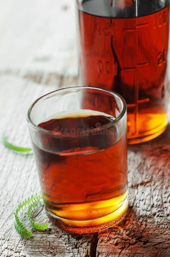Petit verre de boisson alcoolisée ou de teinture médicale sur un fond en bois images libres de droits