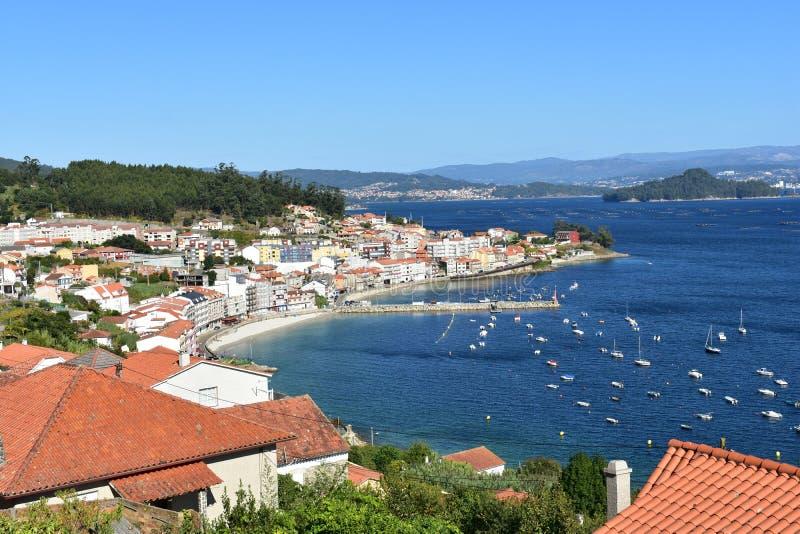 Petit village côtier en baie avec la plage et île avec le pilier de forêt et les bateaux, jour ensoleillé, ciel bleu La Galicie,  photographie stock