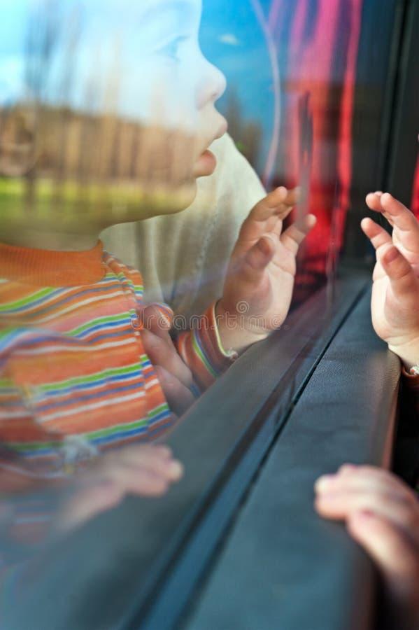 Petit voyageur regardant hors de l'hublot de bus image libre de droits