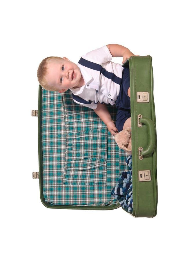 Petit voyageur s'asseyant dans la valise verte photo stock
