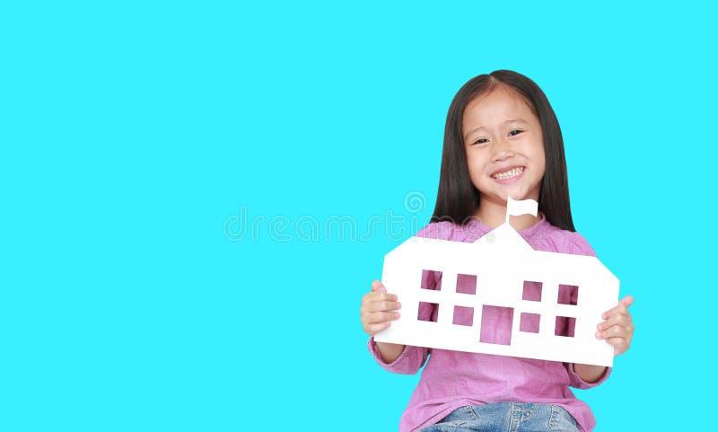Petite école asiatique de sourire de papier de maquette de participation de fille d'enfant d'isolement sur le fond cyan avec l'es photos stock