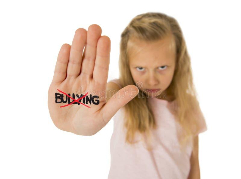 Petite écolière douce et effrayée montrant l'intimidation de mot rayée écrit dans sa main photo libre de droits