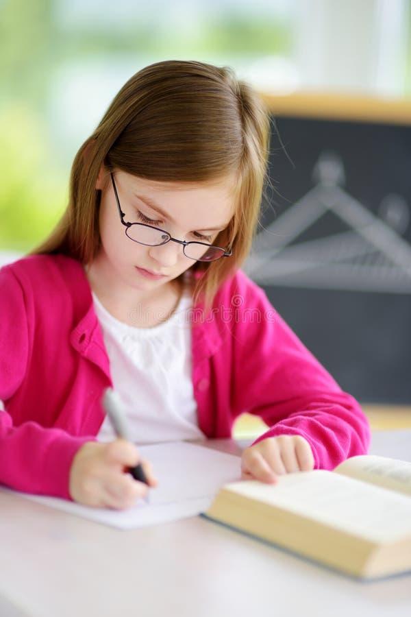 Petite écolière futée avec le stylo et livres écrivant un essai dans une salle de classe photos libres de droits