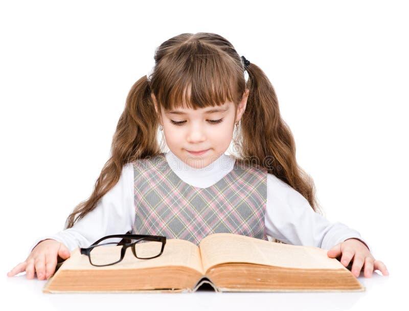 Petite écolière lisant le grand livre D'isolement sur le fond blanc images libres de droits