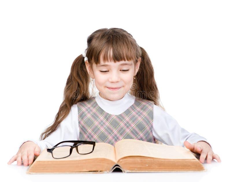 Petite écolière lisant le grand livre D'isolement sur le fond blanc photo libre de droits
