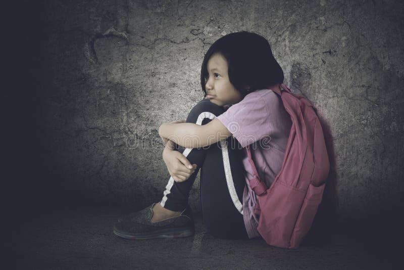 Petite écolière s'asseyant avec l'expression d'effort photo libre de droits