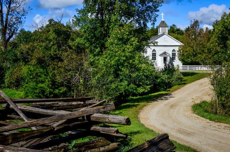 Petite église blanche de pays avec la barrière rustique photographie stock libre de droits