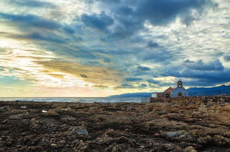 Petite église blanche sur le rivage de la mer de Crète, Grèce Début de la matinée, la coupure dans les nuages de pluie dans le ci photos stock