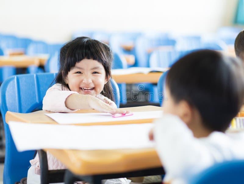 Petite étudiante heureuse dans la salle de classe images stock