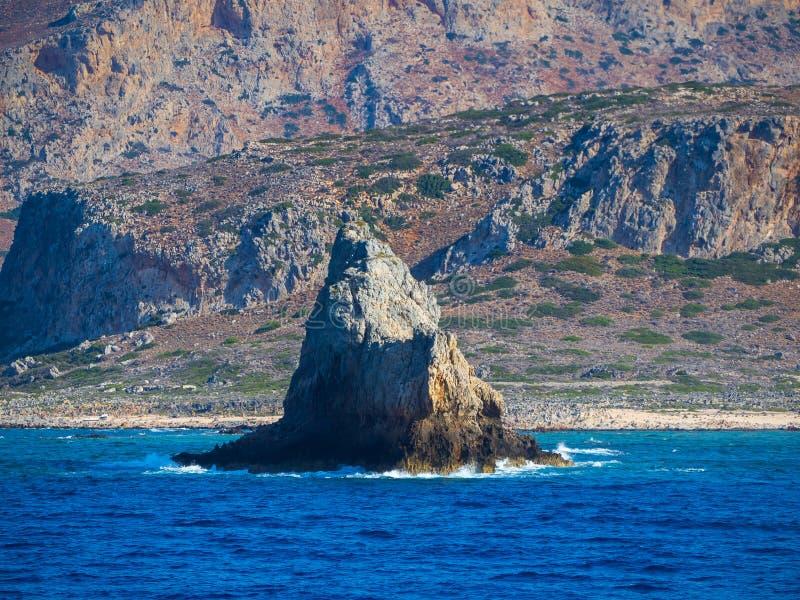 Petite ?le pierreuse - vagues se brisant - grandes falaises rocheuses ? l'arri?re-plan - mer bleue profonde photo libre de droits