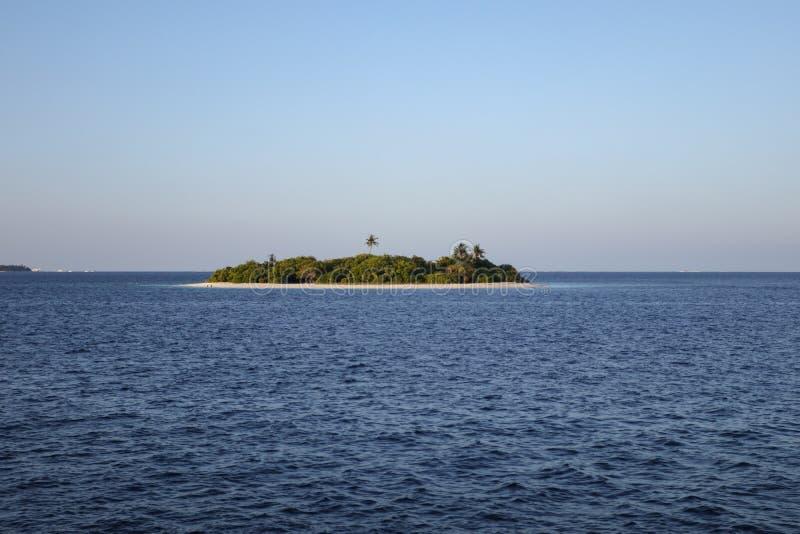 Petite île tropicale dans les eaux bleues de l'océan photographie stock libre de droits